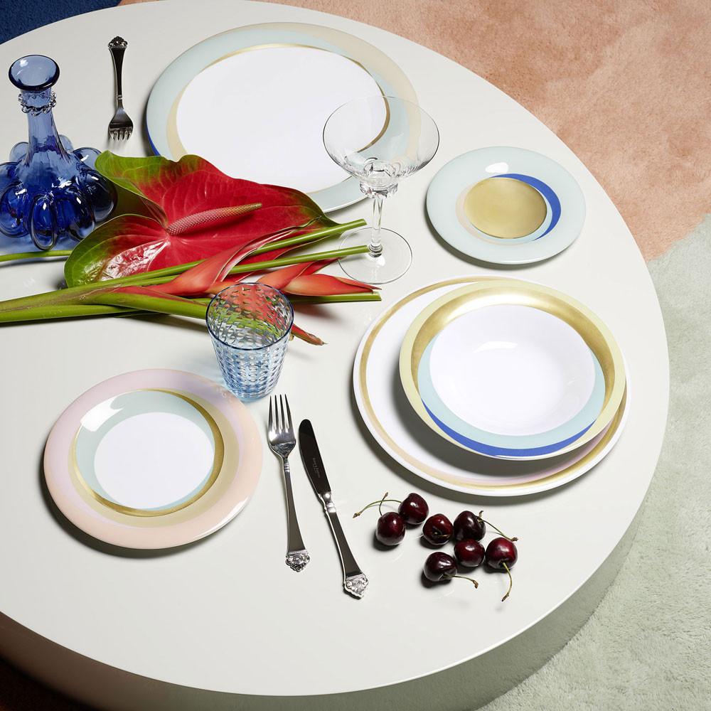 Teller mit farbigem Rand in hellen Farben auf einem weißen Tisch