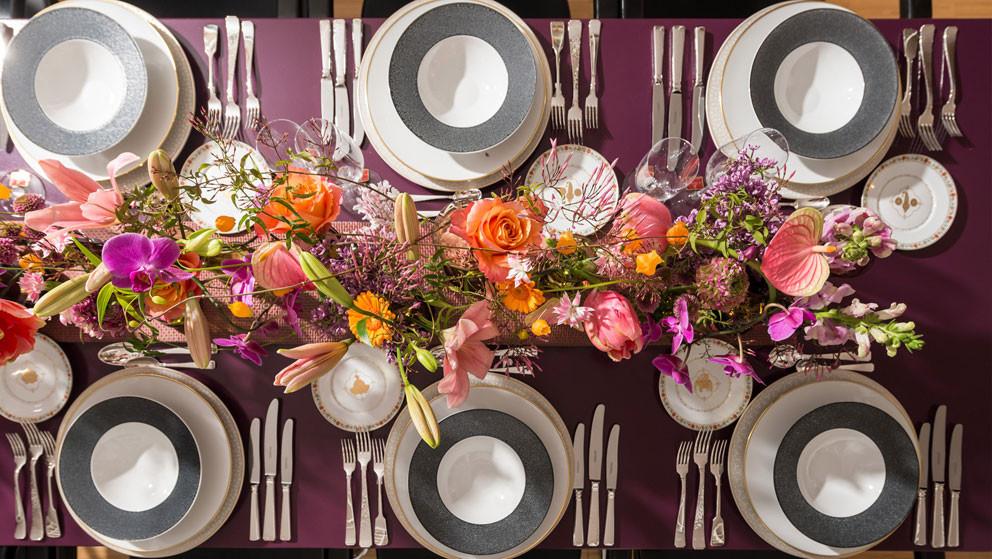 Gedeckter Tisch mit pastellfarbenem Porzellantellern und rosa Besteck, Blumen im Hintergrund