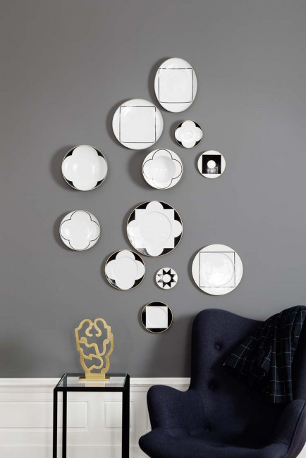 Unterschiedliche Teller der Sieger by Fürstenberg Form My China! mit dem Dekor Ca'd'Oro hängen an einer dekorativen grauen Wand.