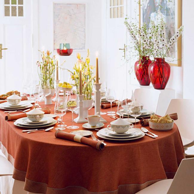 Gedeckter Tisch mit Porzellan und Blumenschmuck, orangene Tischdecke