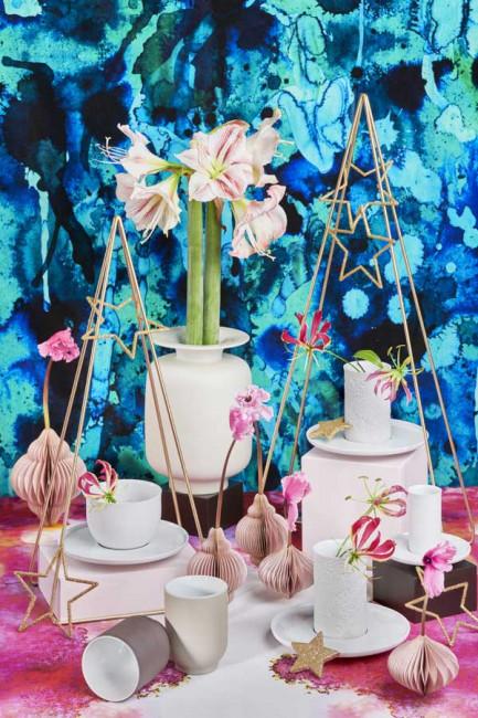 Unterschiedliche Porzellanartikel auf einem rosa farbenen Tisch mit blauer Tapete im Hintergrund