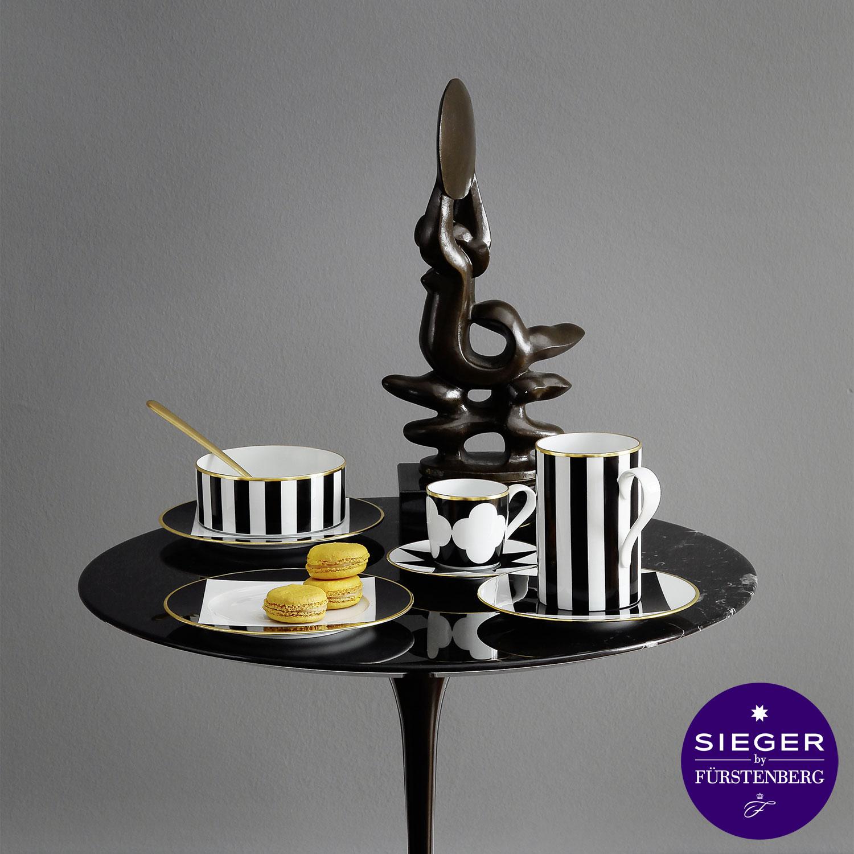 Schwarzes Tischchen mit Teetasse, Espressotasse und kleiner Schale in schwarz-weißem Dekor