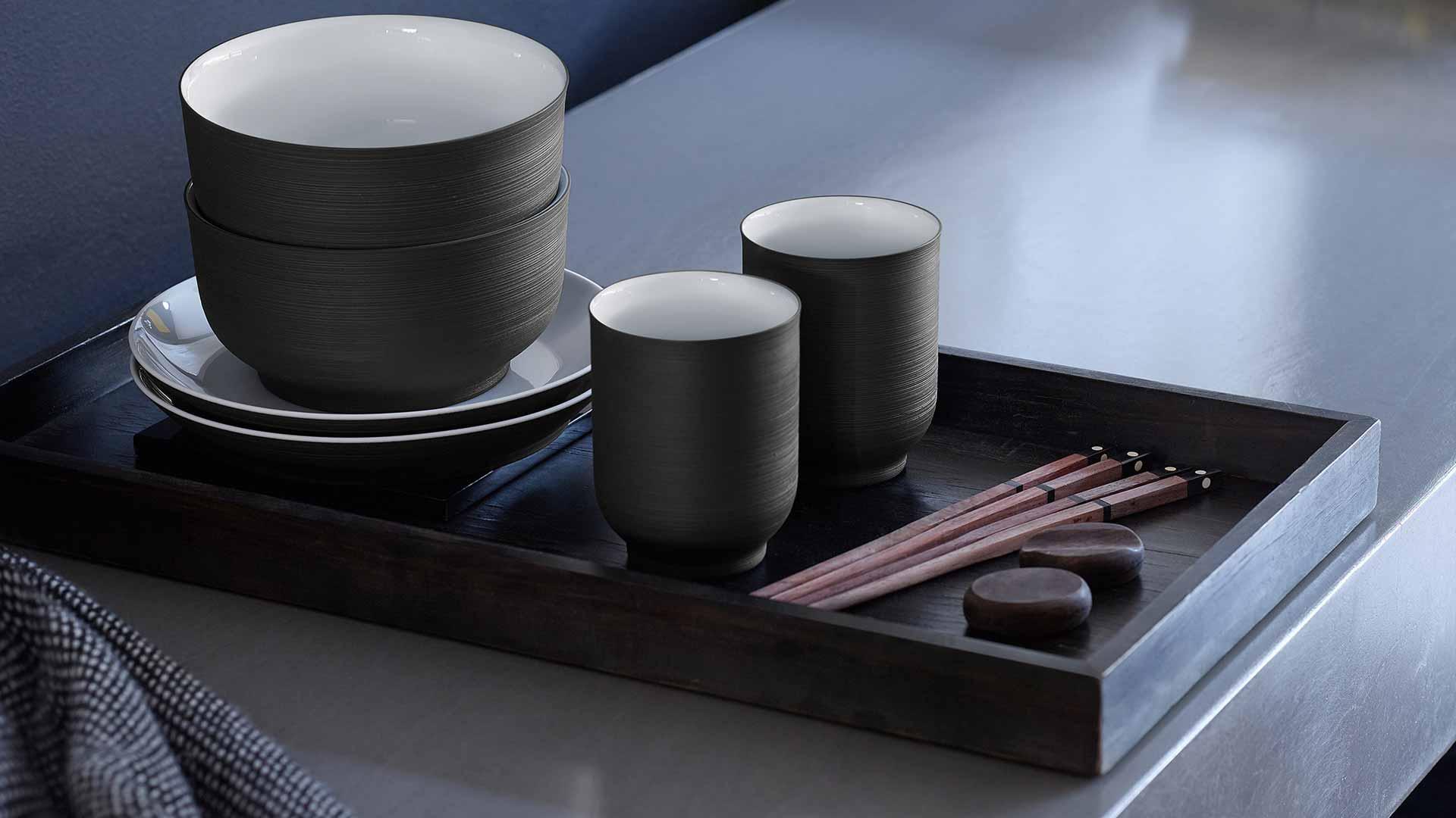 Eine Schale, zwei Becher und Untertassen auf einem kleinen schwarzen Tablett