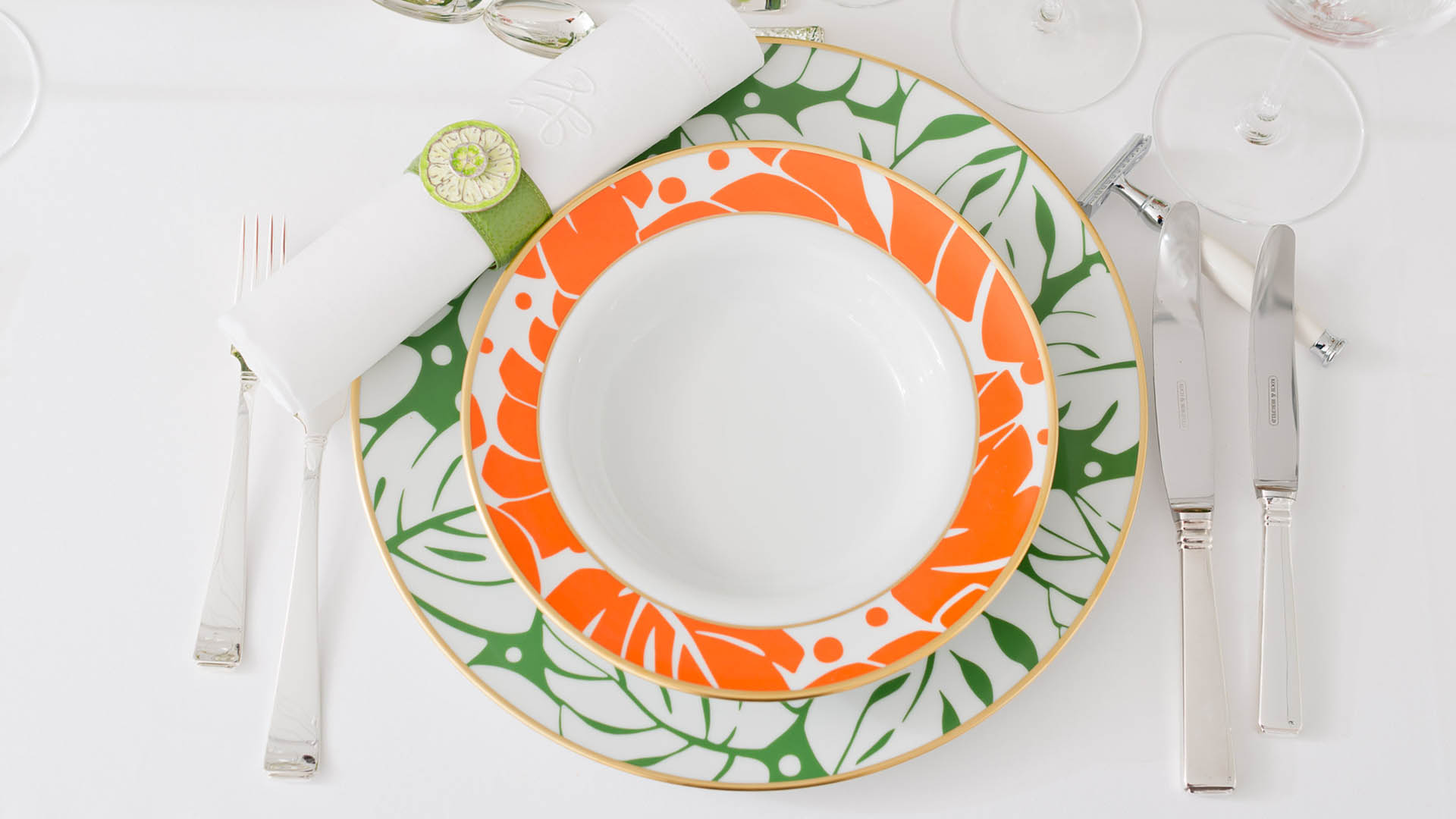 Table with dinner plates and colorful flowers