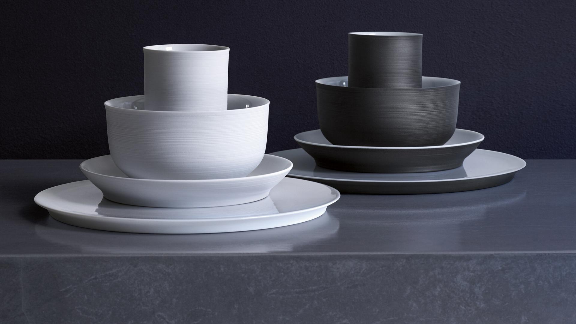 Ein wekißes und ein schwarzes gestapeltes Set aus zwei Tellern, Schale und Becher