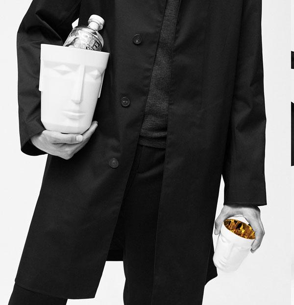 Person nur halb im Bild, die einen Eisbehälter unter dem Arm trägt und einen Becher in der Hand hält