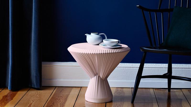 Kleiner Beistelltisch aus rosa Porzellan mit Teekanne und Tasse, daneben ein schwarzer Holzstuhl